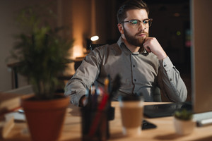 Image of handsome bearded web designer dressed in shirt working late at night and looking at computer.