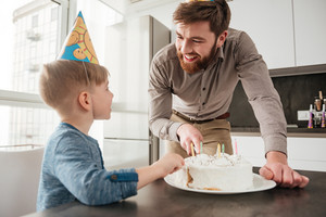Image of handsome happy father cutting the birthday cake of his little son.