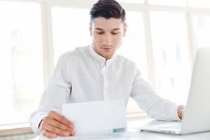 Image of handsome man dressed in white shirt using laptop computer while holding documents. Coworking. Looking at documents.