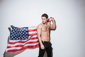 Image of handsome man posing at studio and look away while holding USA flag. Isolated over white background.