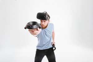 Image of handsome man wearing virtual reality device standing over white background and showing joystick to camera. Look at camera.