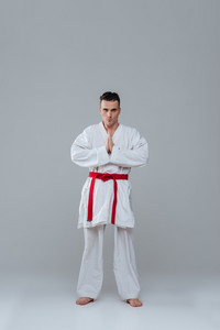 Image of handsome sportsman in kimono practice in karate while posing over grey background. Looking at camera.