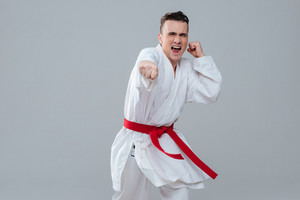 Image of handsome sportsman in kimono practicing at karate while posing over grey background and screaming. Looking at camera.