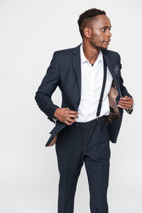 Image of handsome young african businessman posing in studio. Isolated over white background. Look aside.