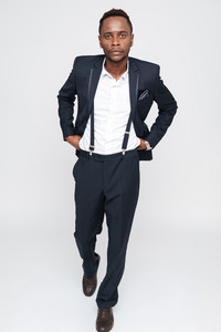 Image of handsome young african businessman posing in studio. Isolated over white background. Look at camera.