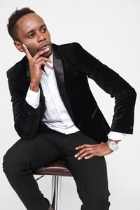Image of handsome young african businessman sitting on stool. Isolated over white background.