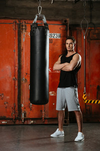 Image of handsome young strong boxer standing in a gym with arms crossed. Looking at camera.