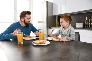 Image of happy bearded father dressed in blue sweater eating at kitchen with his little son