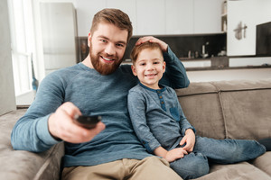 Image of happy bearded father holding remote control while watching TV with his little son.