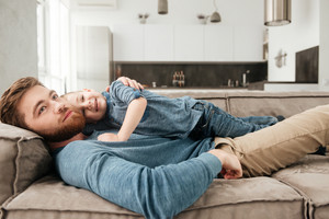 Image of happy bearded father lies on sofa with his little cute son. Look aside.