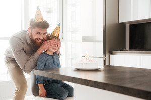 Image of happy bearded young father in the kitchen with his birthday little son covering his eyes.