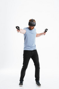 Image of happy bearded young man wearing virtual reality device standing over white background while holding joysticks in hands.