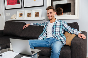 Image of happy bristle man dressed in shirt in a cage print sitting on sofa in home and looking at laptop computer.