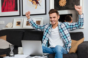 Image of happy bristle man dressed in shirt in a cage print sitting on sofa in home and using laptop computer while stretching.