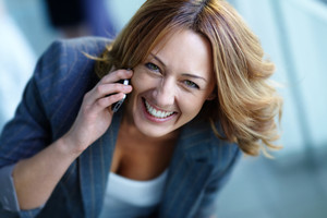Image of happy businesswoman calling on the phone and looking at camera