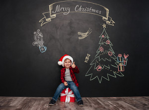 Image of happy child wearing hat sitting on big gift near Christmas tree drawing on blackboard and making thumbs up gesture. Looking at camera.