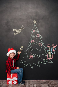 Image of happy child wearing hat sitting on big gift near Christmas tree drawing on blackboard while holding a candy. Looking at camera.