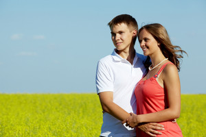 Image of happy couple in yellow meadow embracing