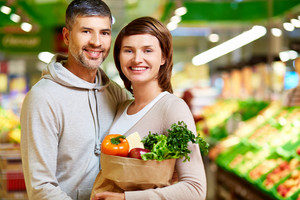 Image of happy couple with paperbag full of products looking at camera in supermarket