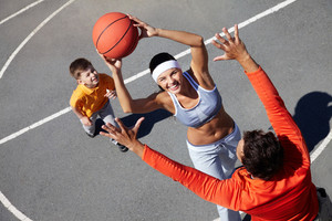 Image of happy female going to throw ball into basket with man and kid near by