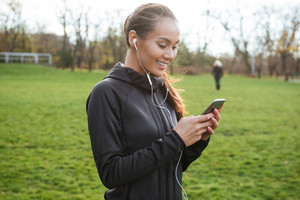 Image of happy female runner in warm clothes in autumn park using her phone