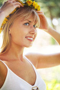 Image of happy female wearing dandelion wreath on summer day