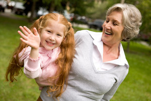 Image of happy girl spending time with her granny outside