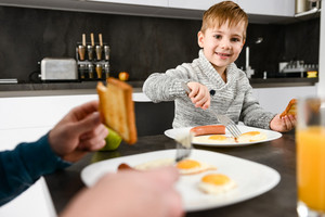 Image of happy little boy eating at kitchen with his father. Focus on boy.