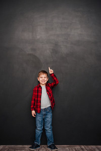 Image of happy little boy standing over chalkboard and pointing up. Looking at camera.
