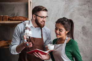 Image of happy loving couple bakers drinking coffee. Looking at notebook.