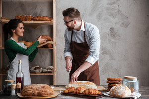 Image of happy loving couple bakers. Looking at each other. Man cut the bread.