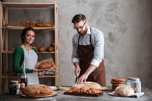 Image of happy loving couple bakers. Man cut the bread. Woman looking at camera.
