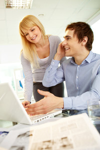 Image of happy man speaking on the phone while his secretary looking at laptop near by in office