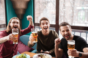 Image of happy men friends sitting in cafe while eating and drinking beer.