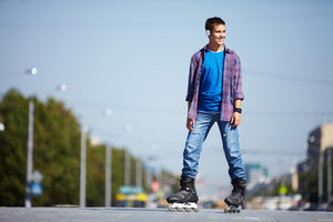Image of happy teenager on roller skates in the city