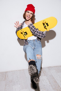 Image of happy woman dressed in shirt in a cage print wearing hat standing isolated over white background holding skateboard