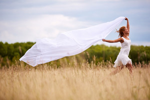 Image of happy woman with white fabric running down meadow