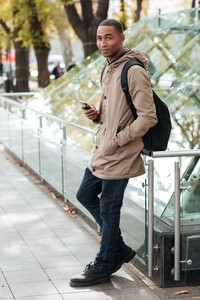 Image of happy young african man holding his phone in hands and looking at camera outdoors.