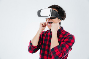 Image of happy young asian man dressed in casual shirt in a cage and wearing virtual reality device and make winner gesture. Isolated over white background.