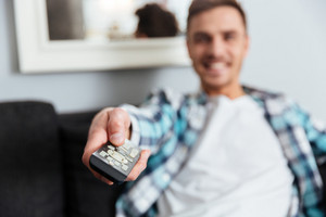 Image of happy young bristle man dressed in shirt in a cage print sitting on sofa in home and holding remote control while watching TV. Focus on remote control.