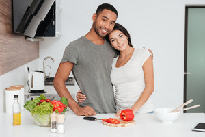 Image of happy young couple in the kitchen hugging while cooking. Looking at camera.