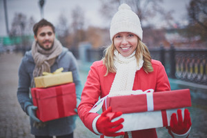 Image of happy young girl with giftboxes looking at camera with her boyfriend behind