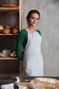 Image of happy young lady baker standing at bakery near bread. Looking at camera.