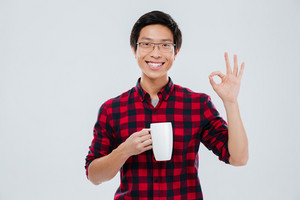 Image of happy young man dressed in casual shirt in a cage and wearing eyeglasses holding cup of tea while making Ok gesture. Isolated over white background. Looking at camera.