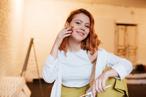 Image of happy young redhead lady painter with oil paints on face in artist workshop. Look at camera.