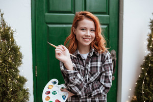 Image of happy young woman painter with red hair. Look at camera while holding palette and paintbrush outdoors.