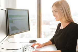 Image of happy young woman worker sitting in office near computer. Looking at computer.