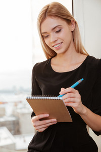 Image of happy young woman worker standing in office holding notebook while writing notes with pen. Look at notebook.
