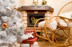 Image of house room with rocking-chair, Christmas tree, fireplace and gifts in it