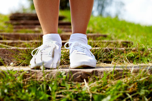 Image of human feet in sportshoes standing on step